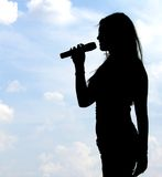 Siluetta della ragazza di canto Fotografie Stock