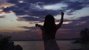 Siluetta della ragazza di dancing al tramonto sulla spiaggia Movimento lento stock footage