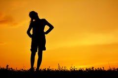 Siluetta della ragazza felice che sta sul campo di erba Immagine Stock