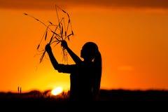 Siluetta della ragazza nel giacimento di grano Fotografia Stock