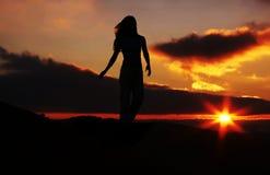 Siluetta della ragazza sul tramonto fotografia stock libera da diritti