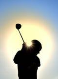 Siluetta della ragazza teenager che oscilla un club di golf Fotografia Stock