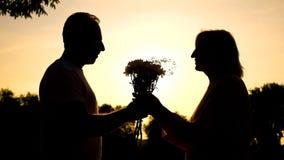 Siluetta della riunione felice delle coppie al tramonto, marito che presenta i fiori alla data immagini stock libere da diritti