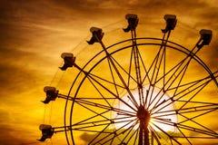 Siluetta della ruota di ferris al tramonto alla fiera della contea Fotografia Stock