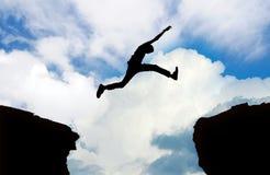 Siluetta della scogliera di salto dell'uomo Fotografia Stock