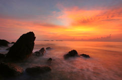 Siluetta della spiaggia della roccia ad alba Immagine Stock