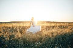 Siluetta della sposa sul giacimento di grano nel tramonto fotografie stock libere da diritti