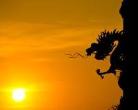 Siluetta della statua del drago con il tramonto. Immagini Stock