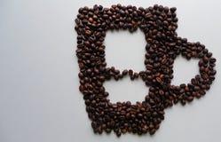 Siluetta della tazza con i chicchi di caffè su fondo bianco immagini stock