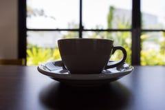 Siluetta della tazza di caffè sulla tavola fotografie stock