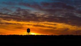 Siluetta della torre di acqua al tramonto Fotografia Stock