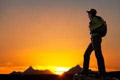 Siluetta della viandante femminile al tramonto. Fotografia Stock