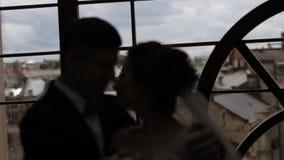 Siluetta delle coppie amorose di nozze vicino alla finestra archivi video