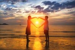 Siluetta delle coppie amorose durante il tramonto stupefacente, tenentesi per mano nella forma del cuore Amore Fotografie Stock