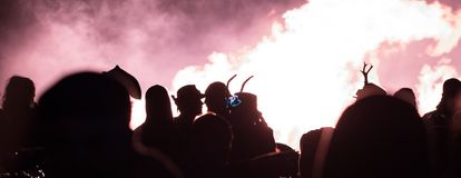 Siluetta delle coppie che baciano davanti ad un fuoco enorme fotografie stock