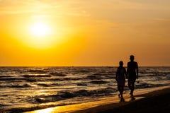 Siluetta delle coppie che camminano sulla spiaggia Fotografia Stock