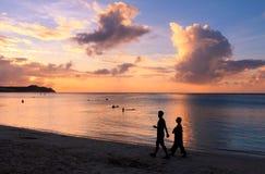 Siluetta delle coppie che camminano sulla spiaggia al tramonto fotografie stock