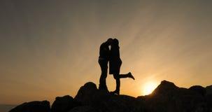 Siluetta delle coppie felici che baciano insieme e che godono del tramonto, guardante in futuro con speranza video d archivio