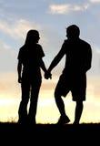 Siluetta delle coppie felici che si tengono per mano sulla passeggiata al tramonto Fotografia Stock