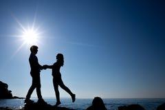 Siluetta delle coppie felici dell'adolescente sulla spiaggia Fotografia Stock