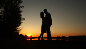 Siluetta delle coppie nell'amore al tramonto Immagini Stock