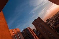Siluetta delle costruzioni di appartamento contro il cielo variopinto al tramonto Fotografie Stock