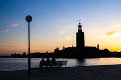 Siluetta delle donne che si siedono sul banco, comune di Stoccolma, svedese immagine stock libera da diritti