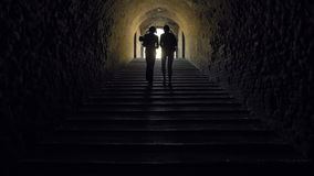 Siluetta delle donne che vanno via in un tunnel scuro video d archivio
