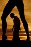 Siluetta delle gambe della donna con il cowboy fra lo sguardo giù Immagini Stock Libere da Diritti