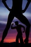 Siluetta delle gambe della donna in mani dei talloni sull'uomo forte delle anche Immagine Stock Libera da Diritti