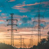 Siluetta delle linee elettriche ad alta tensione contro un cielo drammatico e variopinto ad alba o al tramonto Fotografie Stock Libere da Diritti