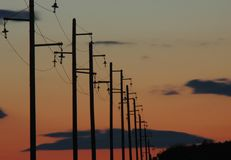 Siluetta delle linee elettriche durante il tramonto fotografia stock