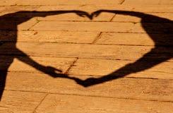 Siluetta delle mani che fanno il cuore del segno sul fondo di legno Immagini Stock Libere da Diritti