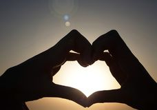 Siluetta delle mani nell'amore sul cielo di tramonto immagine stock libera da diritti