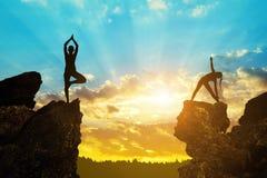 Siluetta delle ragazze che fanno yoga su una roccia Fotografie Stock Libere da Diritti