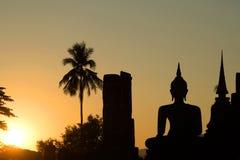 Siluetta delle sculture antiche del Buddha messo al tramonto Sukhothai thailand fotografie stock libere da diritti