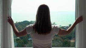 Siluetta delle tende di rivelazione della giovane donna e guardare dalla finestra Godendo della vista del mare fuori archivi video