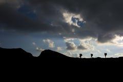 Siluetta delle viandanti con gli zainhi che scalano la montagna Immagine Stock