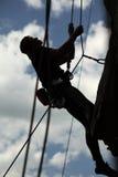 Siluetta dello scalatore di roccia che si abbassa giù la scogliera Immagini Stock