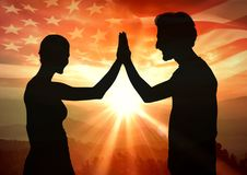 Siluetta di alto fiving della gente contro il tramonto e la bandiera americana Immagine Stock