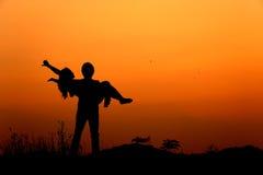 Siluetta di amore della donna e dell'uomo nel tramonto Fotografie Stock Libere da Diritti