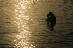 Siluetta di amore tenero della madre e del bambino alla spiaggia che prendono il sole alla luce dorata durante il tramonto Fotografia Stock