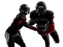 Siluetta di azione del gioco di passaggio di due giocatori di football americano fotografia stock libera da diritti