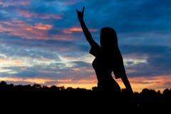 Siluetta di bella donna sexy sui precedenti del tramonto Immagini Stock