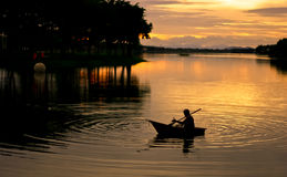Siluetta di canottaggio del pescatore Immagini Stock