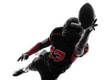 Siluetta di cattura della palla del giocatore di football americano fotografia stock