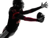 Siluetta di cattura della palla del giocatore di football americano fotografia stock libera da diritti