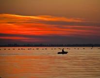 Siluetta di Fisher sulla barca al tramonto Fotografie Stock Libere da Diritti
