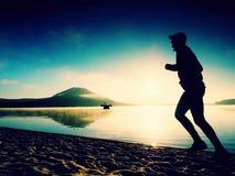 Siluetta di funzionamento attivo dell'uomo di sport sulla spiaggia del lago ad alba Stile di vita sano Immagine Stock