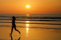 Siluetta di funzionamento del pareggiatore della donna sulla spiaggia di tramonto con la riflessione, la forma fisica e lo sport fotografie stock libere da diritti